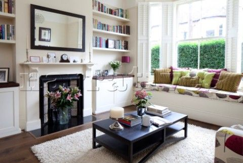 Recessed bookshelves with Victorian fireplace in living room with upholstered window seat in London