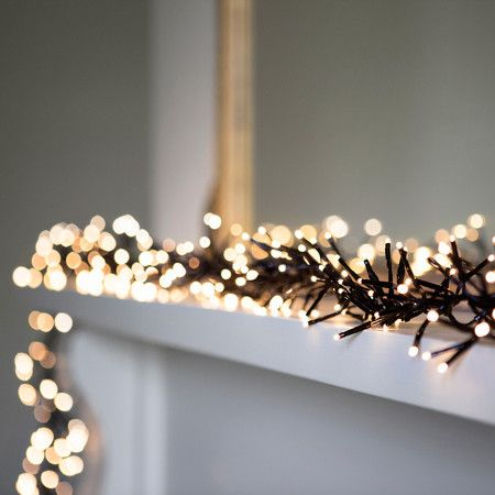 """Warm White LED Cluster Fairy Lights On Black Cable -- """"Dress your home in style with this gorgeous warm white cluster garland, the perfect addition to any winter wonderland. Ideal for candy cane wrapping around large Christmas trees and laying atop fireplaces"""""""