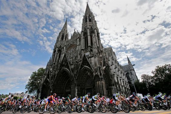 The pack passes a church in Rouen during the start of the fifth stage of the Tour de France cycling race over 196.5 kilometers (122 miles) with start in Rouen and finish in Saint-Quentin, France, Thursday July 5, 2012. (AP Photo/Christophe Ena)