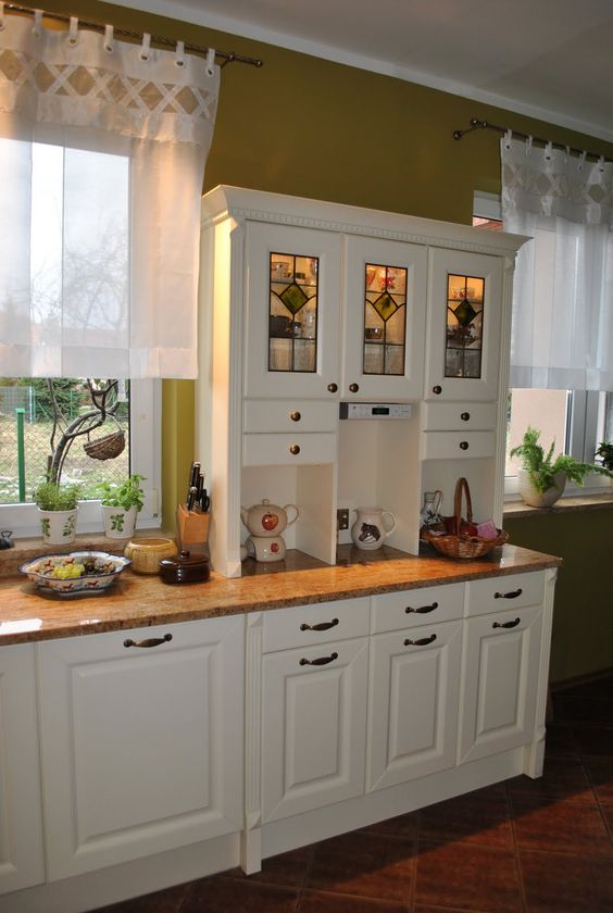 English Country Style Dark Green and White Kitche with Beautiful Window Types that have White Transparent Style Upper Curtains and Minimalist White Wood Wall Mounted Cabinet also Simple Base Cabinet that have Brown Countertop for Design Ideas