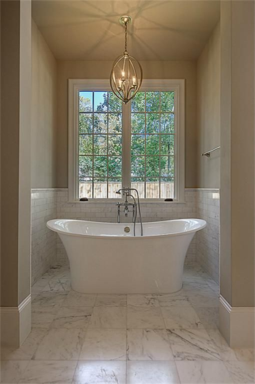 Marble subway tile wainscot surrounds a graceful victoria albert white