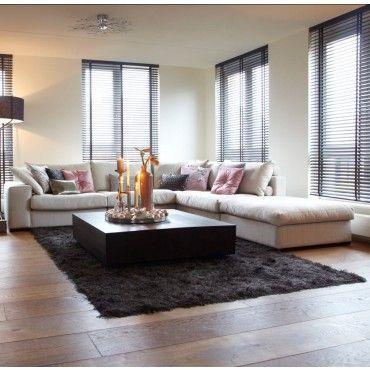 Beige modular lounge, black floor rug, wood floors