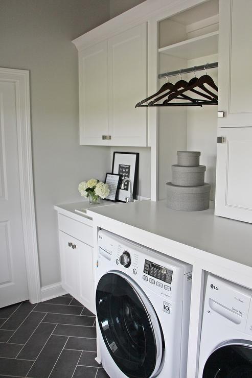 White laundry room with gray herringbone floor