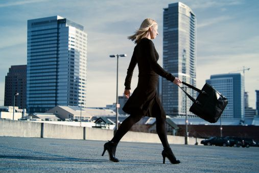 High-Res Stock Photography: young business woman walks across a parking…