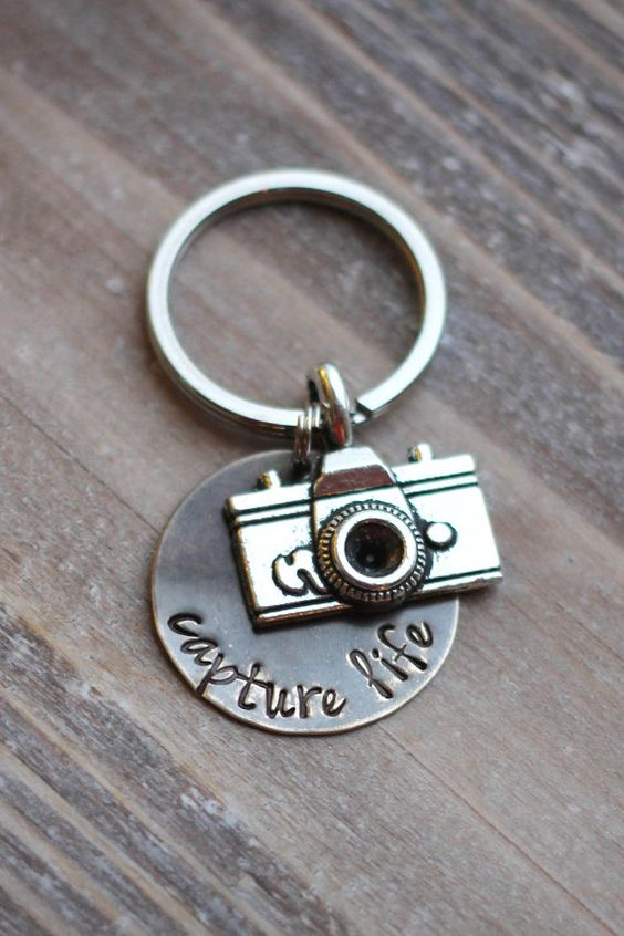 This is a key chain made out of a vintage brass circle with the words capture life hand stamped onto it. It also has a silver camera charm and