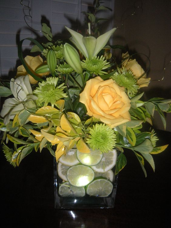 The use of fruit, bold colored flowers and decorative floral wire makes this centerpiece come alive.