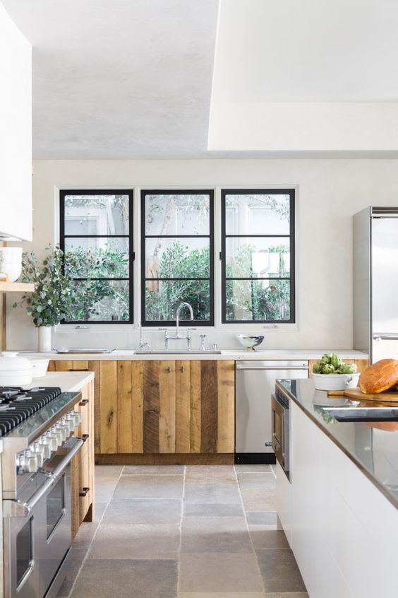 The kitchen sink and fridge in Leigh Herzig's Spanish villa kitchen are conveniently situated alongside a central island, which is topped with stainless steel and has its own integrated sink.