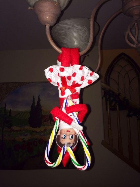 Elf on a shelf with a candy cane heart.