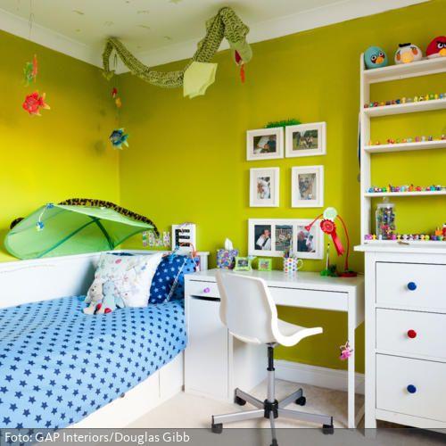 Ist die Wandfarbe knallig, darf im Kinderzimmer auch noch die bunte Kinderdeko hinzukommen. Bunte Girlanden und Mobiles, Schirme in Blattform fürs Bett, Bilderrahmen, Kuscheltiere und was das Kinderherz noch begehrt. Während die Wand in Gelbgrün gehalten ist, bleiben die Möbel weiß.