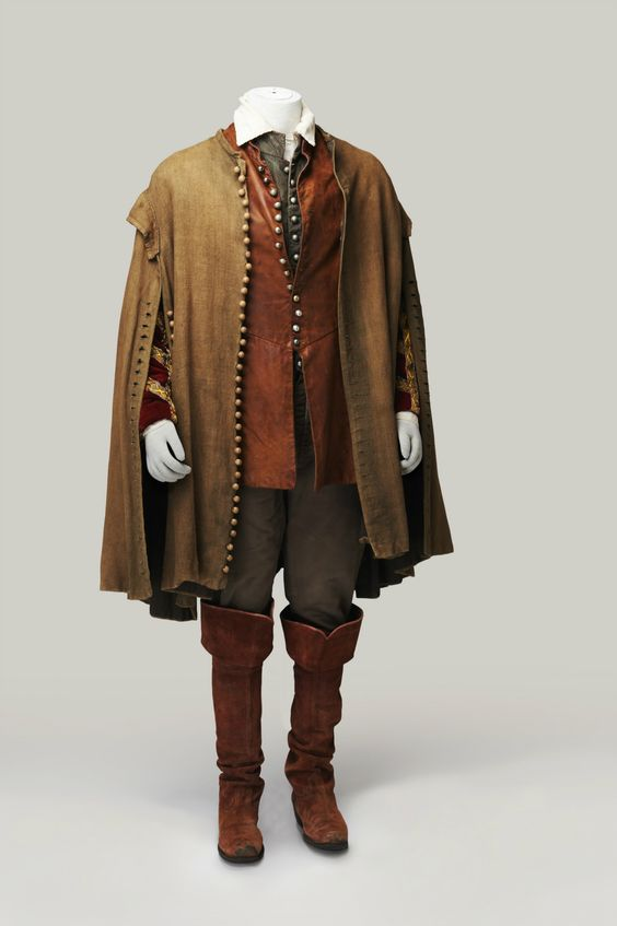 Completo maschile che consta di camicia in battista, farsetto marrone cotto, pantaloni grigi e mantella marrrone chiaro. Il tutto estremamente resistente. Costo £60