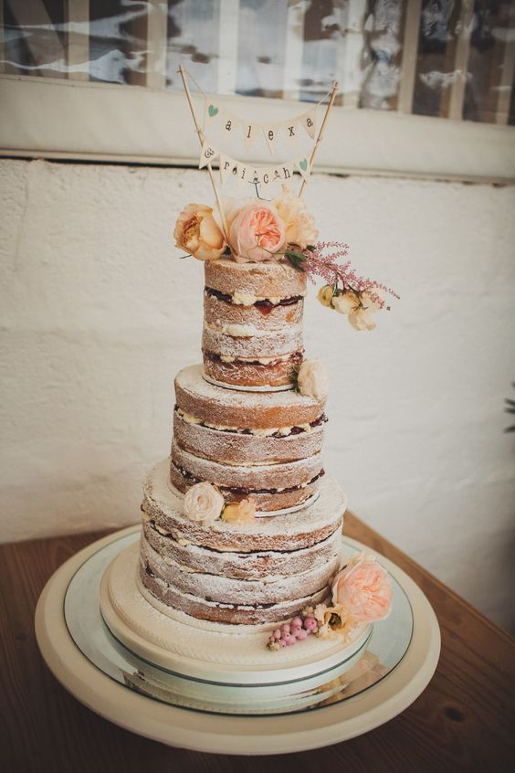 Naked wedding cake with mini bunting cake topper - Image by Ali Paul Photography - Bohemian wedding dress from Grace loves Lace at a laid back coastal beach wedding in Cornwall. Bridesmaids wear duck egg blue dresses from H&M and groomsmen wear jeans, flip flops and braces.