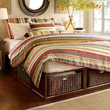 Esta cama aprovecha el espacio debajo con cajones de mimbre para lugar de guardado.