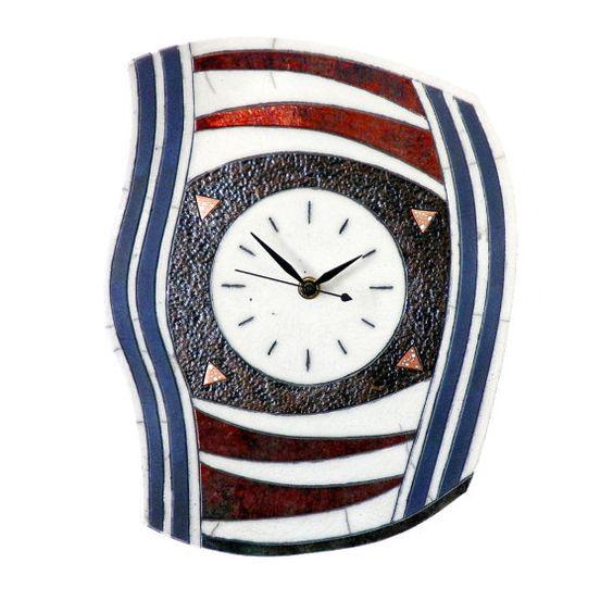 Belle horloge murale en céramique raku. Entièrement faite à la main, les reflets cuivrés de la glaçure ainsi que son design la rendent