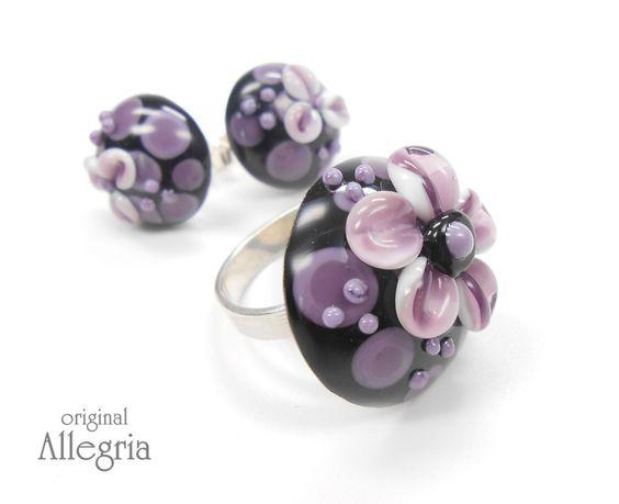 blümchenring in wunderschönem violett auf schwarz.... Die Ringschiene ist 925er Sterlingsilber in Juwelierqualität mit tollem Tragekomfort. Die Ringgrösse ist variabel einstellbar. Die...