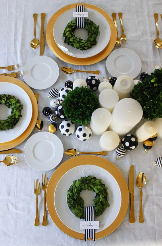 Black, gold and white holiday decor! We used boxwood topiaries, pillar candles, DIY black & white polka dot ornaments and Sugar Paper's gift topper ornament sets fromTarget to create  this year's Christmas decorations for our table. For each place setting we used a mini boxwood wreath, a black and white striped ribbon and a simple place card. We gold chargers, gold flatware and white china.: