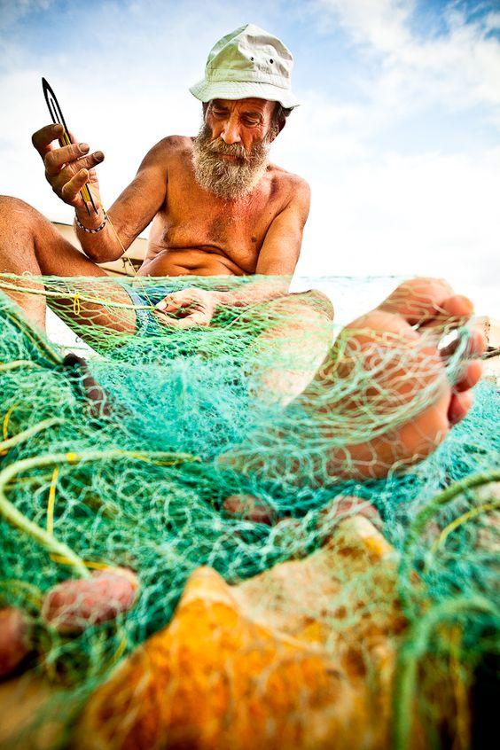 Greek fisherman mending his nets