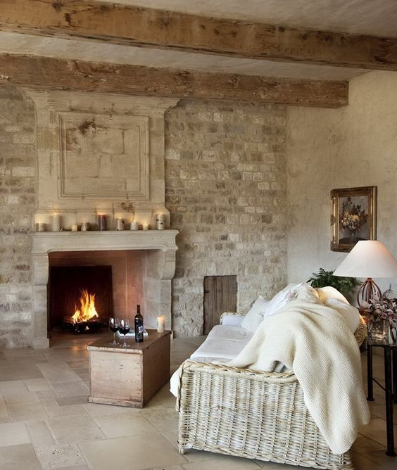 Rustic, cozy, and romantic living room with fireplace, stone wall and wood beams. European Farmhouse and French Country Decorating Style Photos. #europeancountry #europeanfarmhouse #rusticdecor #frenchcountry #livingroom #provence #oldworld #stone