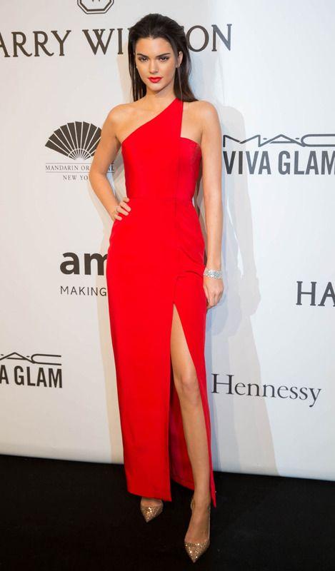 Kendall Jenner en la Amfar Gala lució un vestido asimétrico con abertura en la pierna en color rojo. Acompañó su 'look' con una melena 'wet' hacia atrás.