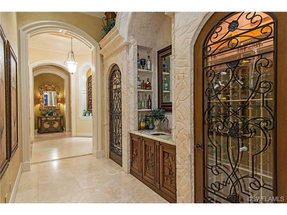 Wine cellar - iron and glass and wood doors.  Grey Oaks Naples, Florida
