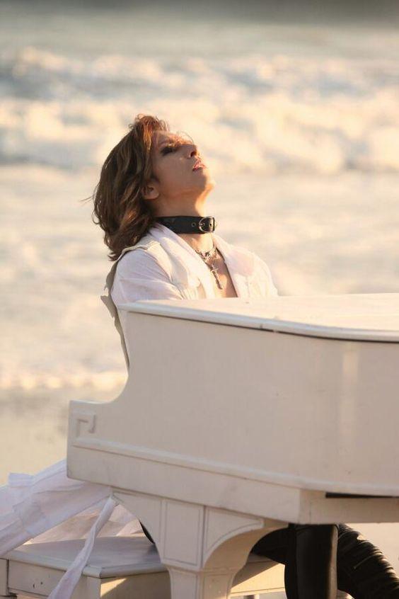 海をバックに白いグランドピアノを弾いているXJAPAN・YOSHIKIの画像