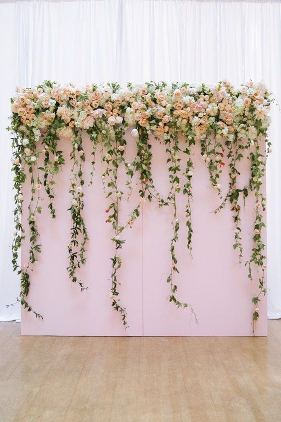 The lush floral backdrop adds glamour and romance to a indoor wedding ceremony. photo: Jasmine Lee::