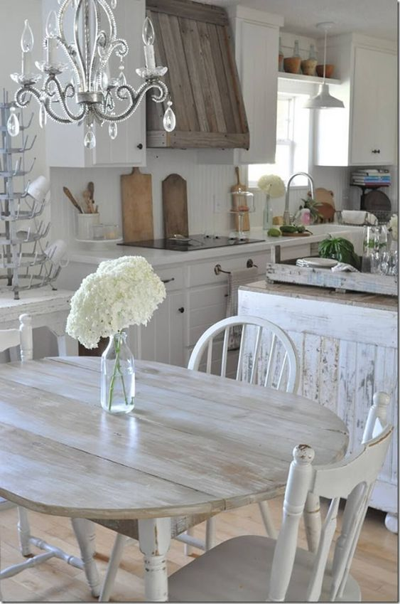 Whitewashed Wooden Table and Chairs in a European country kitchen with chandelier and bottle drying rack. #rustic #whitekitchen #Swedish