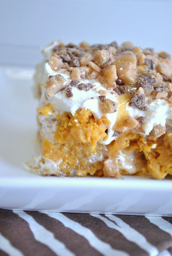 Unbelievable Pumpkin Cake~  soaked in sweetened condensed milk, smothered in cool whip, caramel, and heath bits on top!