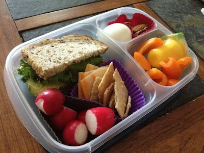 Left: Quinoa patty sandwich with avocado and romaine lettuce on grainy bread, cheddar cheese & crackers, radishes. Top right: medium-boiled egg, almonds. Bottom right: mango jelly thing, orange pepper slices. All packed in an EasyLunchbox.