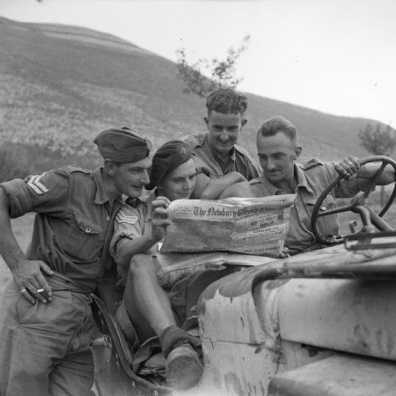 British troops read a paper in their jeep, Italy, 1943.