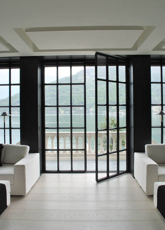 A grid of black steel doors leading to waterfront balcony for Window design with steel