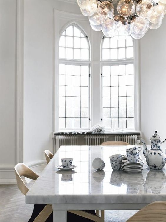 love the tall arched windows, herringbone floors, great light fixtures and marble table top