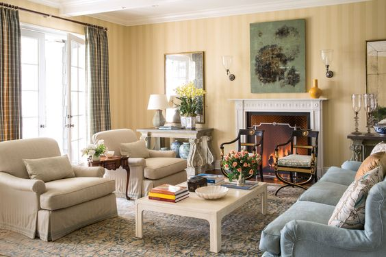 The living room is organized in pairs--two Georgian tables under identical mirrors by Jasper, two Regency chairs with Egyptian motifs and clear glass sconces--creating a soothing symmetry in front of the fireplace. Painting by Charles Fine. A pale blue sofa slipcovered in a damask fabric sits beside the parchment coffee table.
