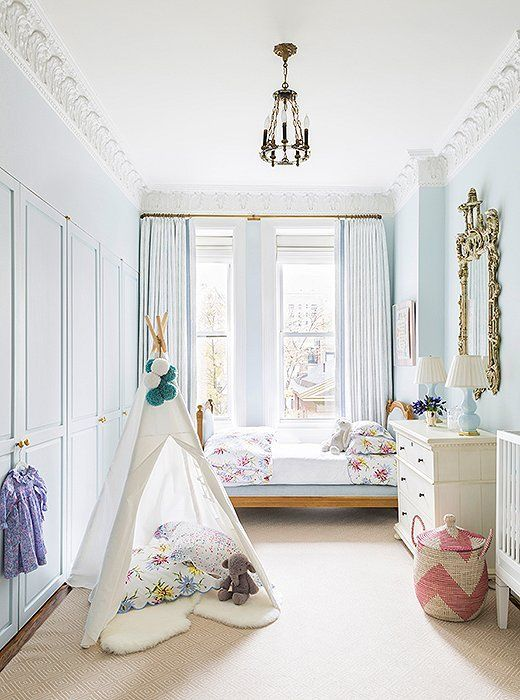"Walls in Farrow & Ball's Borrowed Light set a restful tone in the girls' room, with hints of lively color added mainly through sweet accessories. ""I wanted to create a space that was peaceful and beautiful for my daughters and really not too childish—because I knew that once the toys started to fill the room that the kiddie aspect would take care of itself."" Another goal for the space: practicality. Scotchgard protects the light-colored wool rug from spills, and durable outdoor upholstery ensure"