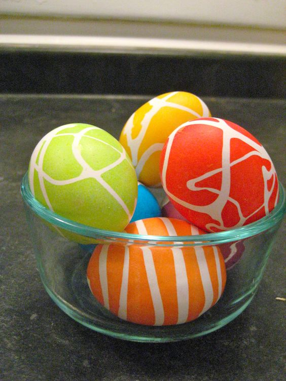 Drip rubber cement over hardboiled eggs before dying (neon food coloring and let eggs sit for 5 minutes to make them BRIGHT!)