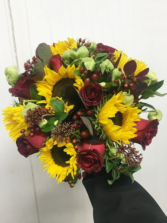 Bridal Wedding Bouquet with Yellow Sunflowers, Red Roses, Hypericum and Hellebores Winter Bells. Autumnal September Wedding at Easton Grange Wedding Venue in Suffolk. For more information on Flowers visit www.trianglenursery.co.uk or for a Wedding Florist in Suffolk, visit https://visit.trianglenursery.co.uk/wedding-consultation/