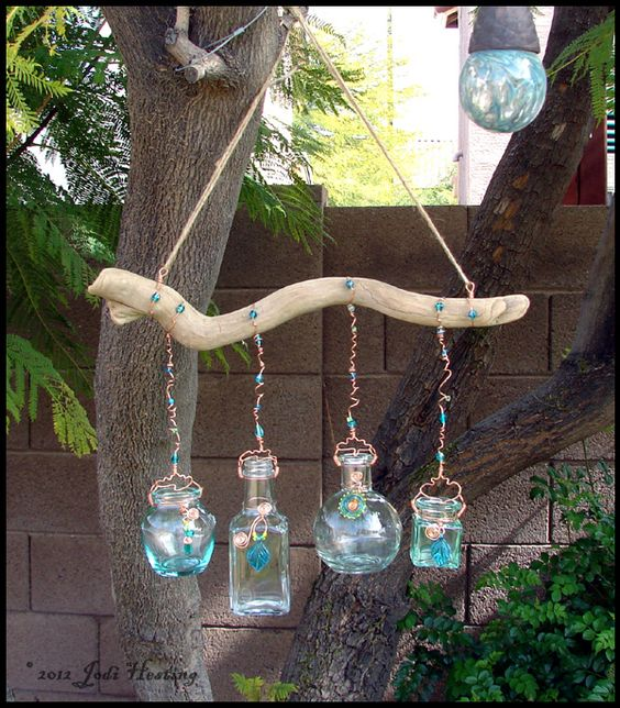 Garden art. Bottles I collected at thrift stores and a piece of driftwood I found. Copper wiring and some of my handmade lampwork beads too! Easy DIY project! And great to put some of the flowers from your garden in!
