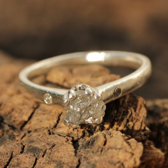 Sterling silver hand textured ring with genuine rough diamond and pave set diamond on either side of the main gem
