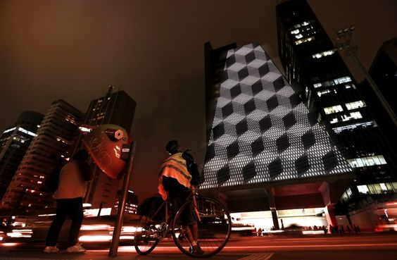 """A cyclist looks at a video game projected on the surface of the Fiesp building during the """"Play!"""" exhibition in Avenida Paulista"""