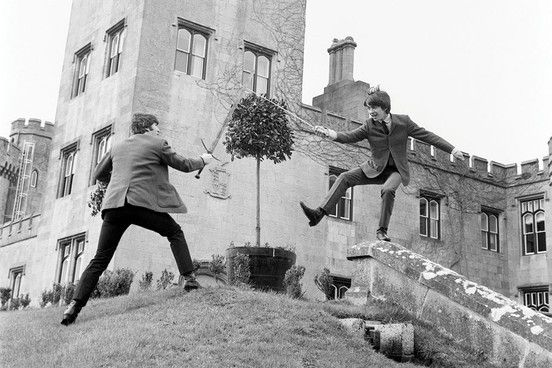 George displays his impressive sword balancing skills with John at Dromoland Castle in Ireland. Ringo was hiding inside the Olive tree. 27th March, 1964.