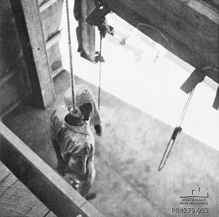 The body of a Japanese war criminal as seen through the trapdoor of the gallows immediately after he was executed by hanging at the Changi Gaol in Singapore. His hands have been tied behind his back and he wears all white, including a hood over his head. Note the semicircles marked on the visible half of the trapdoor, which match up to form full circles indicating where those about to be hanged should stand. (1946) Via the Australian War Memorial