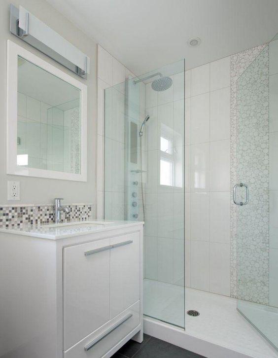 petite salle de bains avec un carrelage en blanc et beige, porte de douche en verre et meuble sous-vasque blanc