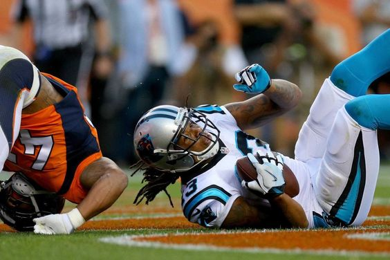 Wide receiver Kelvin Benjamin #13 of the Carolina Panthers catches a 14-yard touchdown reception in the first quarter against strong safety T.J. Ward #43 and cornerback Chris Harris #25 of the Denver Broncos at Sports Authority Field at Mile High on Sept. 8, 2016 in Denver.