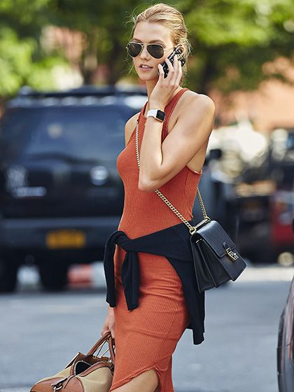 Karlie Kloss on the street in NYC wearing an orange jersey dress with a black sweater tied around her waist and aviator sunglasses (2015)