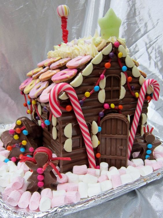 Chocolate bar candy house decorated with marshmallows and cookies.