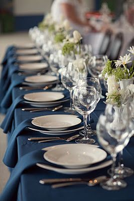 Dark Blue linen instead of white. Maybe custom made napkins in a cool vintage or plaid pattern, over rattan chargers