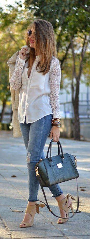 Ella esta llevando una par pantalones con camisa blanco y ella tiene una bolsa…