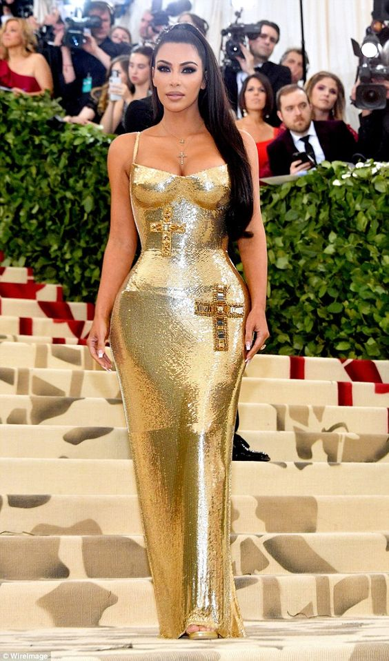 Kim Kardashian makes gold great again in busty gown at Met Gala (but leaves Kanye West at home)