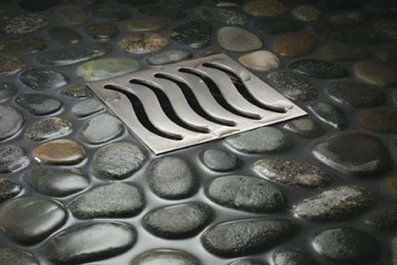 Washroom floor covered in Dark River Pebbles with floor angled toward drain(s). They would be placed above a black stained concrete floor, and the pebbles set in clear resin.