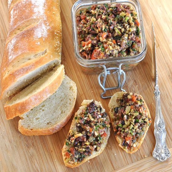 Three Olive Tapenade 1 cup kalamata olives, pitted 1 cup large green olives, pitted 1 cup California olives, pitted 1 each red bell pepper, roasted and cut into 1″ pieces (see instructions below) 4-5 cloves of garlic 1/2 oz parsley, loosely chopped 1/2 oz basil, loosely chopped 3 tsp lemon juice 2 Tbsp capers 5 Tbsp olive oil