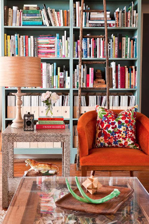 pale blue shelves  bright multi-colored cushion on chair  orange textured fabric (velvet) on chair?  the green antler on the table.  note that the lampshade and side table are rather neutral, as are the magazine holders in the bookshelf. IOW it's not an onslaught of color. Just some touches that contrast nicely and keep it interesting and happy.